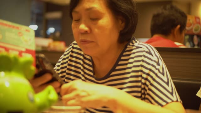 vídeos de stock, filmes e b-roll de mulher sênior em um restaurante. - idoso na internet
