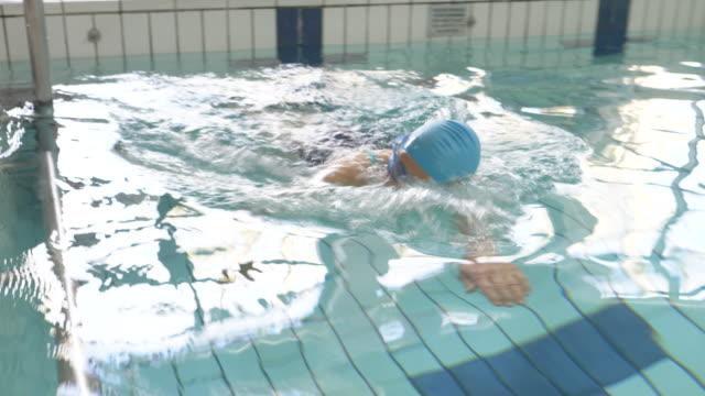 vídeos de stock e filmes b-roll de senior woman in an indoor swimming pool - touca de natação
