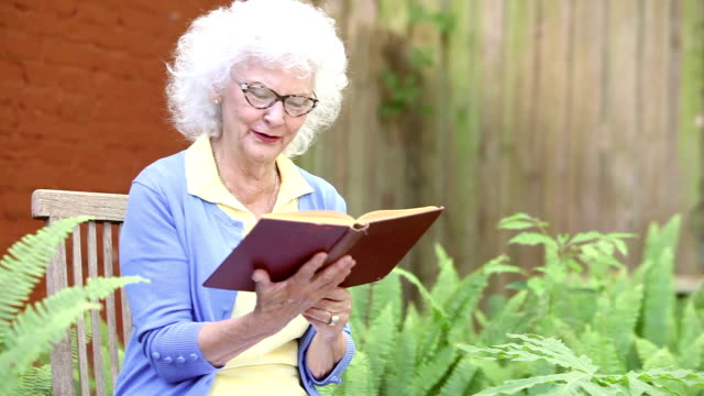 senior woman in back yard reading book - white hair stock videos & royalty-free footage