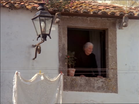 Senior woman in black leaning out of window of home / Oridos, Portugal