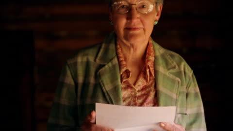 vídeos y material grabado en eventos de stock de ms portrait senior woman in eyeglasses holding open letter + looking at camera indoors - correspondencia