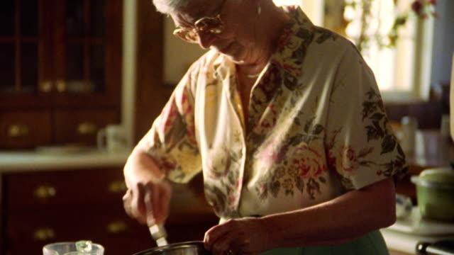 vídeos y material grabado en eventos de stock de ms senior woman in eyeglasses stirring mixture in metal bowl in kitchen - mujeres mayores