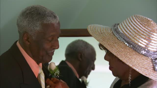 cu senior woman in hat putting corsage on senior man / halifax, nova scotia - ネクタイ点の映像素材/bロール