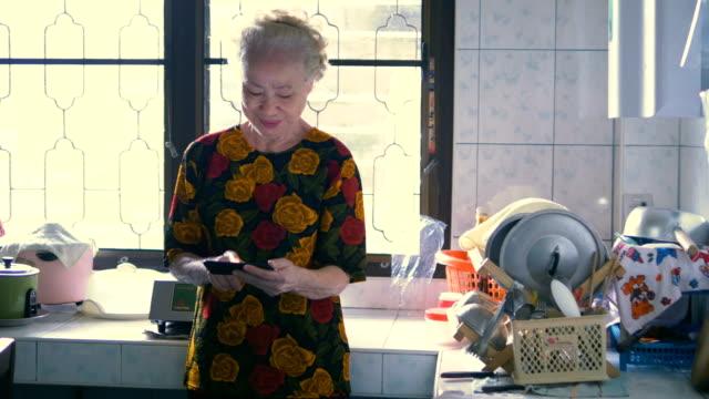 senior woman in kitchen - routine stock videos & royalty-free footage