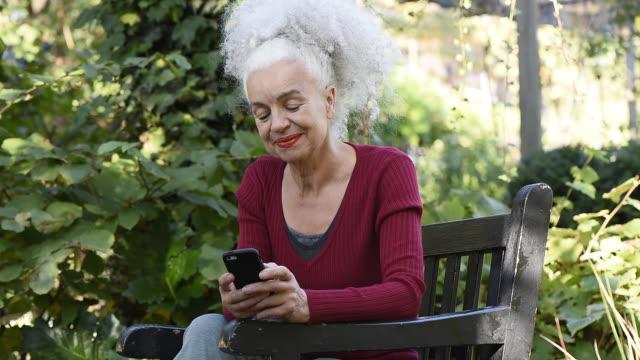 stockvideo's en b-roll-footage met senior woman in park using mobile phone - haar naar achteren