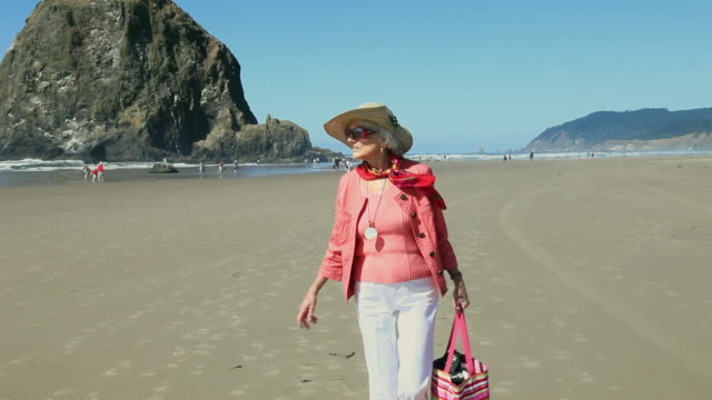 vídeos y material grabado en eventos de stock de ms pov senior woman in pink jacket walking on beach / portland, oregon, usa - 80 89 años