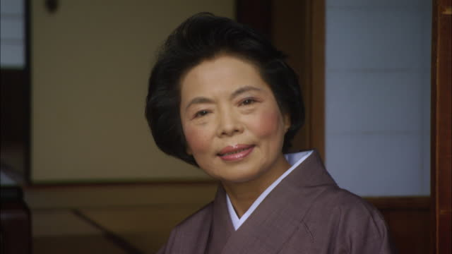 cu focus portrait senior woman in robe bowing/ tokyo, japan - senior women点の映像素材/bロール