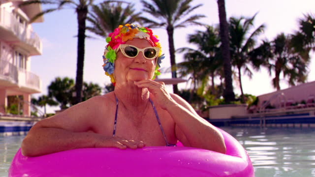 MS senior woman in sunglasses + colorful flowery bathing cap smiling in pink inner tube in pool