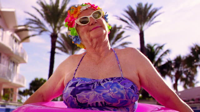 MS senior woman in sunglasses + flowery bathing cap in pink inner tube in pool / palm trees in background