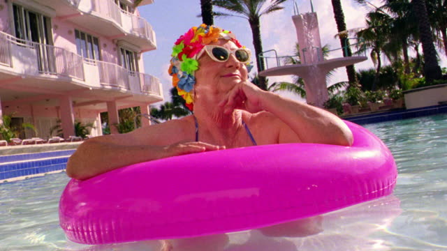 CANTED MS senior woman in sunglasses + flowery bathing cap in pink inner tube in pool smiling