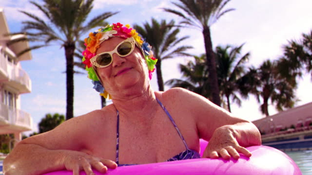 MS senior woman in sunglasses + flowery bathing cap stands up from pink inner tube in pool smiling