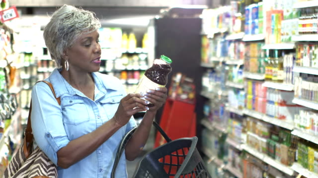 senior woman in supermarket reading food label - shopping basket stock videos and b-roll footage