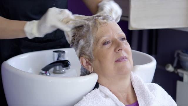 senior woman  in the hair salon - shampoo stock videos & royalty-free footage