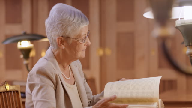 LD Senior woman in the library leafing through a book