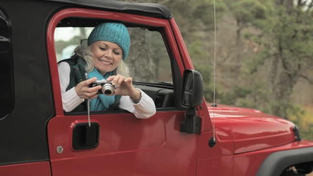 senior woman in vehicle using digital camera - digital camera stock videos & royalty-free footage