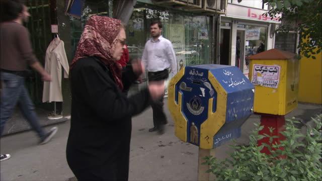 ms senior woman inserting money into donation box on sidewalk, tehran, iran - donation box stock videos & royalty-free footage