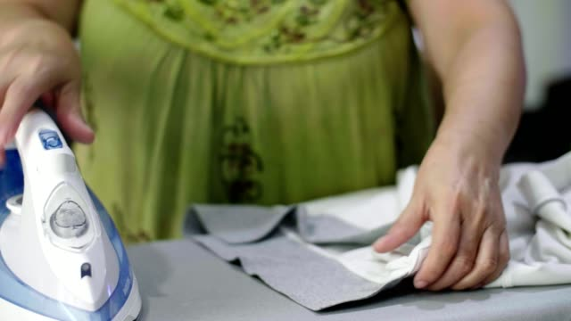 cu: 年配の女性の服にアイロンを自宅のアイロン - アイロン点の映像素材/bロール