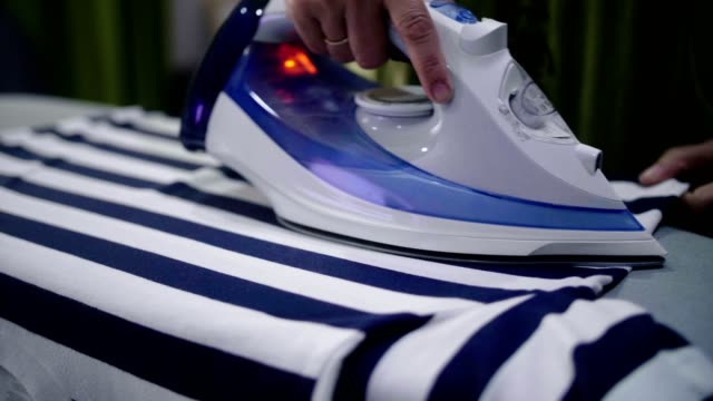 cu : senior woman ironing clothes on ironing board at home - iron appliance stock videos & royalty-free footage