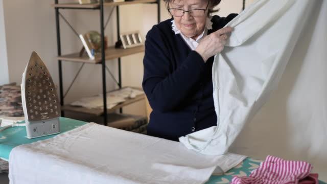 自宅で洗濯物にアイロンをかけるシニア女性 - 退職と家の仕事 - アイロン点の映像素材/bロール