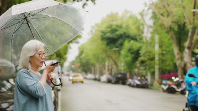 Senior woman is waiting for a taxi on a rainy day in the city