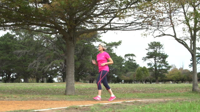 senior woman jogging in a park - one senior woman only stock videos & royalty-free footage