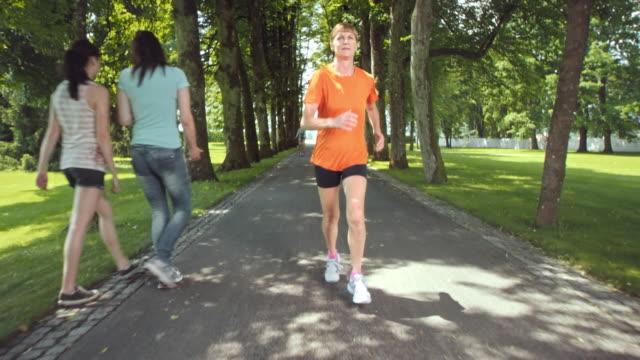 vidéos et rushes de slo missouri ts senior femme jogging à travers l'arbre avenue - 55 59 ans