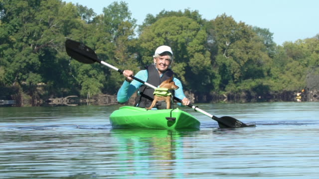 senior woman kayaking with her dog - ruderboot stock-videos und b-roll-filmmaterial