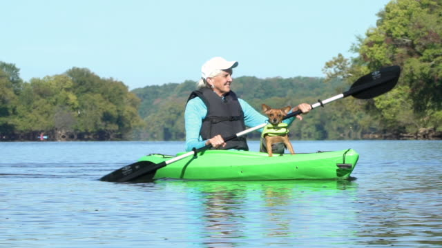 Senior woman kayaking with her dog