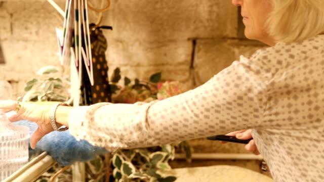 vídeos de stock, filmes e b-roll de loja de manutenção da mulher senior limpo - pano de pó