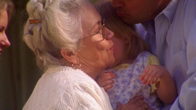 MS senior woman kissing blonde girl toddler (man holding girl) / girl smiling + clapping