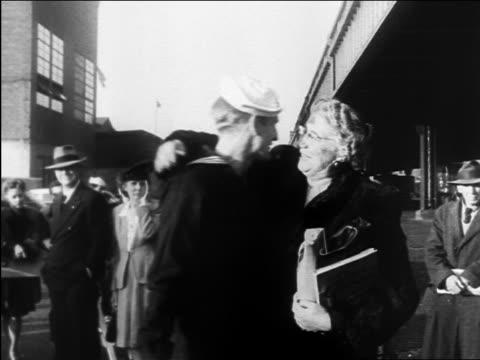 vidéos et rushes de b/w 1945 senior woman kissing sailor hello / crowd in background / ww ii homecoming / documentary - marinière