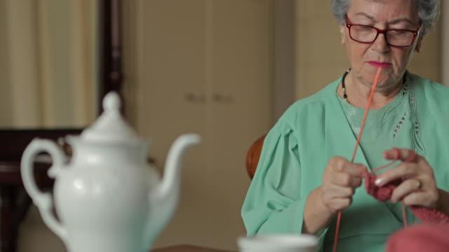 vídeos y material grabado en eventos de stock de senior mujer tejer mientras se relaja en casa. - tejer