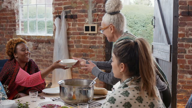 senior woman ladling soup into bowl for friend - dining room stock videos & royalty-free footage