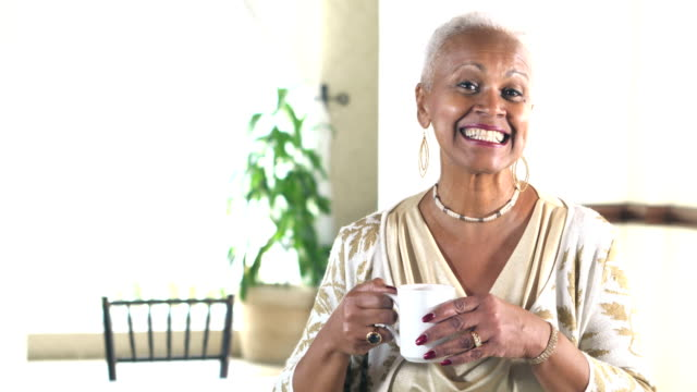 Senior woman laughing, looking at camera, with coffee