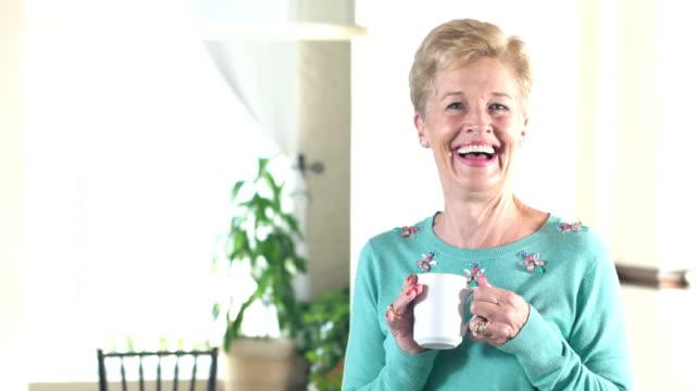 stockvideo's en b-roll-footage met senior vrouw lachen, kijken camera, met koffie - 70 79 jaar