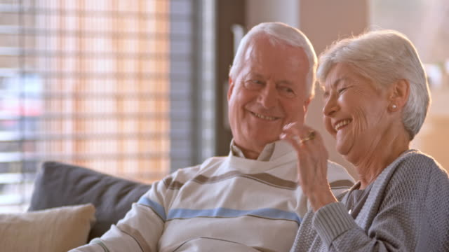 slo mo senior woman laughing while watching tv with her husband - living room stock videos & royalty-free footage