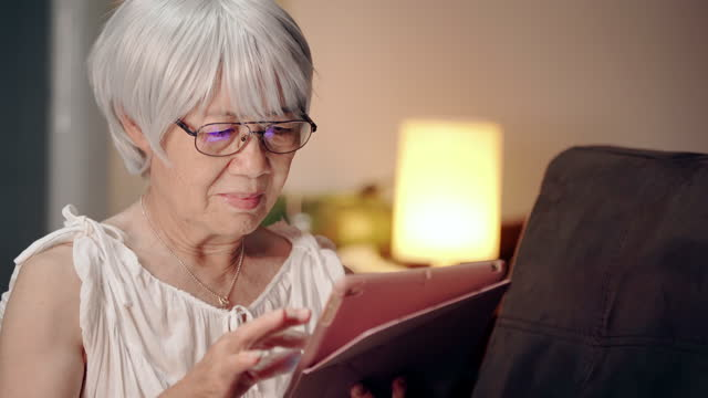 senior woman learning with digital tablet at her home. grandma using social teleconferencing with her family - grandmother stock videos & royalty-free footage