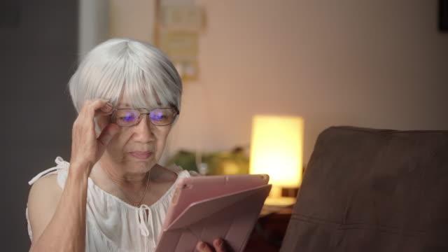 vídeos de stock e filmes b-roll de senior woman learning with digital tablet at her home - objeto manufaturado
