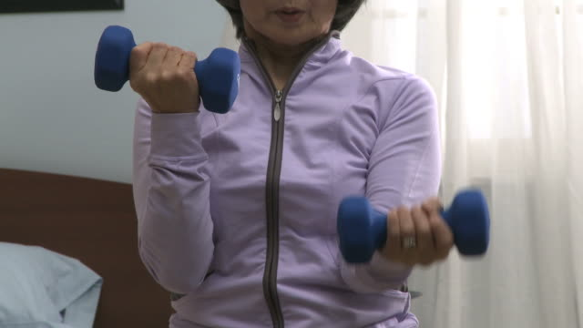 senior woman lifting dumbbells in her bedroom - sportswear stock videos & royalty-free footage