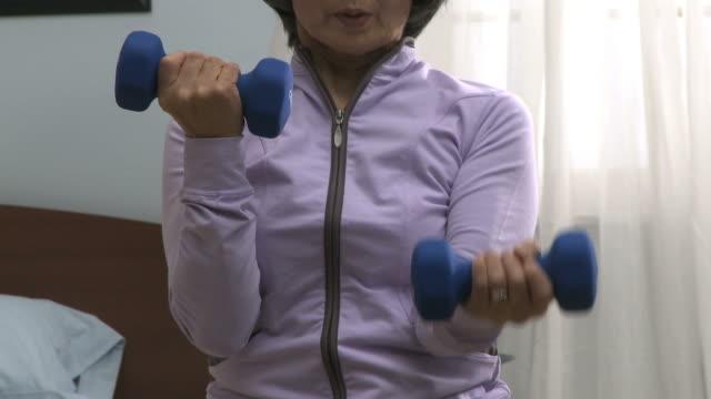 senior woman lifting dumbbells in her bedroom - sportkleidung stock-videos und b-roll-filmmaterial