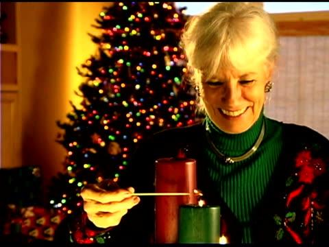 Senior woman lighting Christmas candles