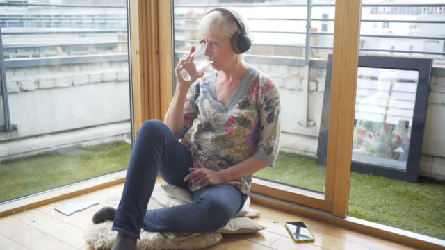 a senior woman listening intently to a podcasts - kurzes haar stock-videos und b-roll-filmmaterial