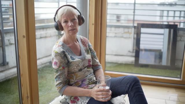 vidéos et rushes de a senior woman listening intently to a podcasts - une seule femme d'âge mûr