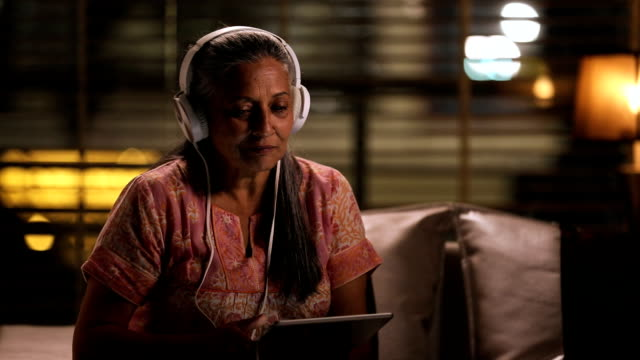 Senior woman listening music on headphone, Delhi, India