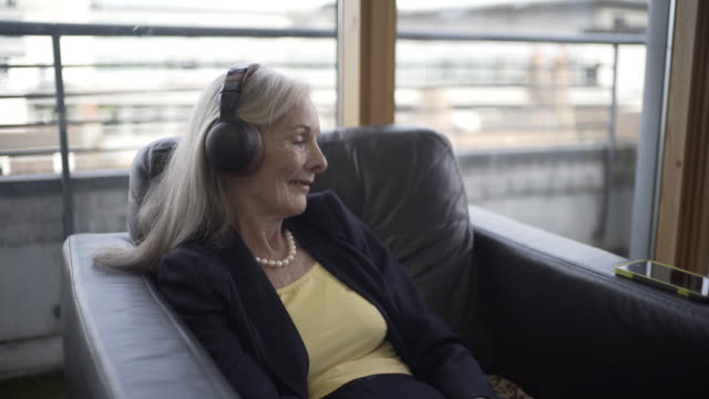 A senior woman Listening to a podcast.