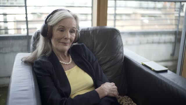a senior woman listening to a podcast. - red nail polish stock videos and b-roll footage