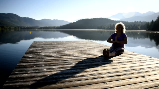 senior woman living an active lifestyle - sun salutation stock videos and b-roll footage