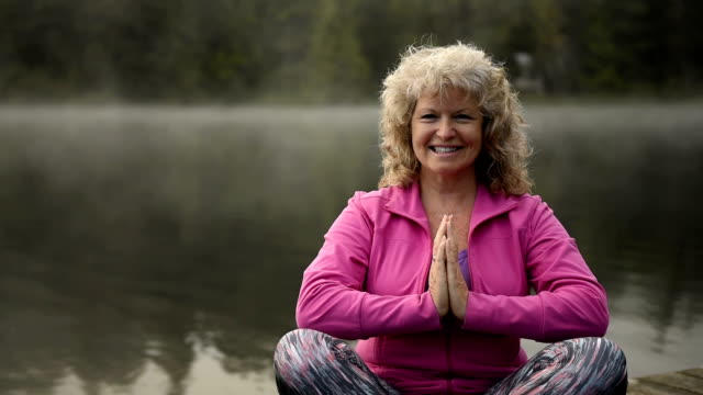 senior woman living an active lifestyle - sun salutation stock videos & royalty-free footage
