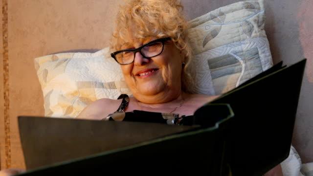 Senior woman looking at an old photo album brings back memories