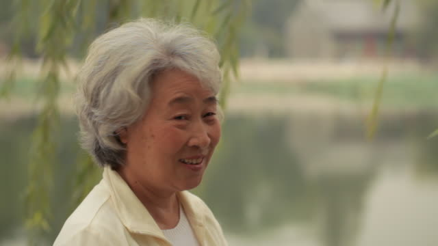 ms senior woman looking at camera and smiling by the lake / china - chinese ethnicity stock videos & royalty-free footage